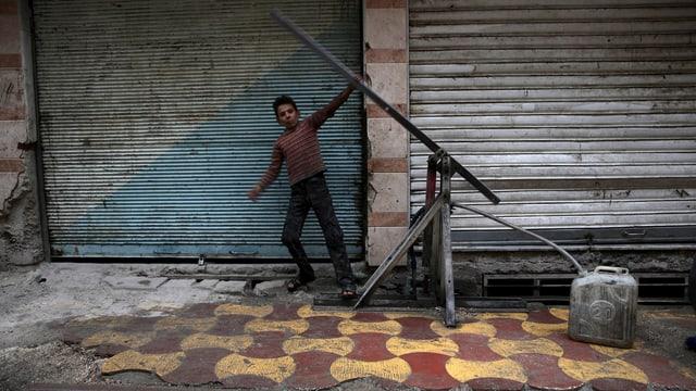 Ein Junge pumpt in einer Strasse in Damaskus Wasser in einen Kanister.