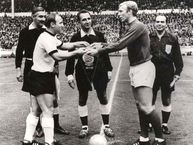 Der Schweizer Schiedsrichter Gottfried Dienst sieht zu, wie die beiden Captains Uwe Seeler und Bobby Moore Wimpel austauschen. Hinten links steht Assistent Tafik Bachramow.