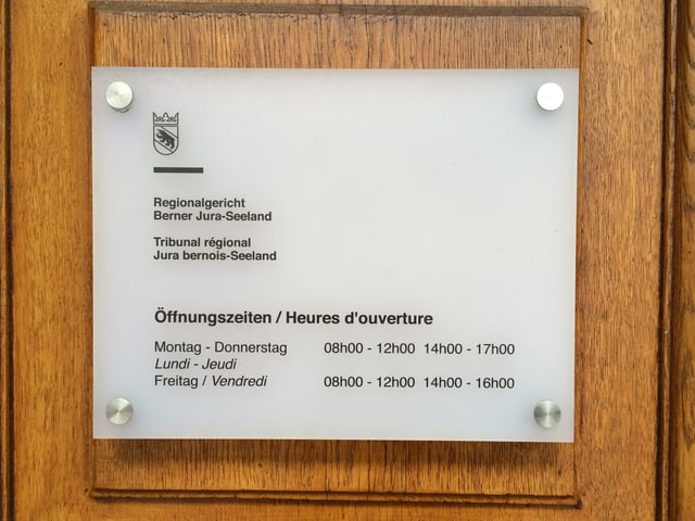 Tafel mit Öffnungszeiten am Gerichtsgebäude in Biel.