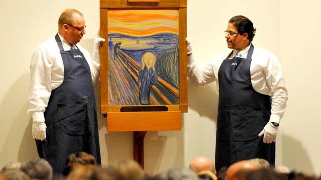 """In der Mitte das Bild """"Der Schrei"""" von Edvard Munch, gehalten von zwei Mitarbeitern des Auktionshauses, die Handschuhe und Schürzen tragen."""