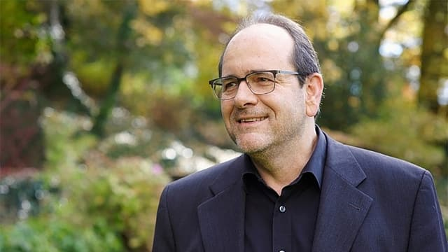 Ein Mann in Anzug und Brille, dahinter Wald.
