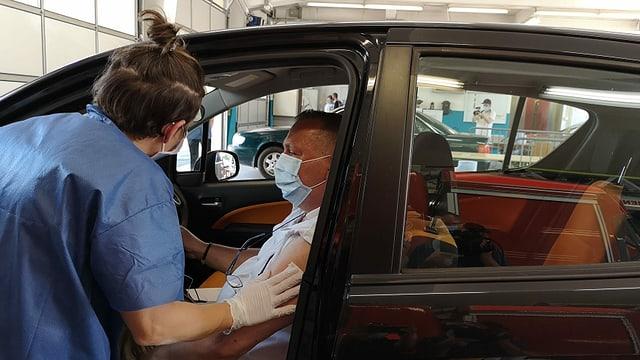 Frau wischt druch Auotüre mit Tüchlein Oberarm von Mann in Auto ab.