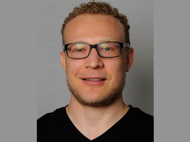 Porträt eines jungen Mannes mit Brille.