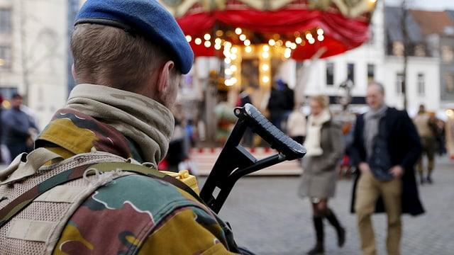 Symbolbild: Bewaffneter Soldat vor einem beleuchteten Karussell.