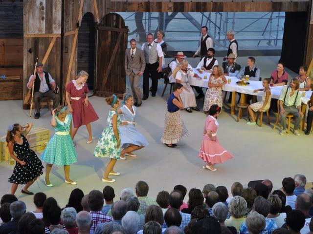 Schauspieler tanzen und singen auf der Musical-Bühne.