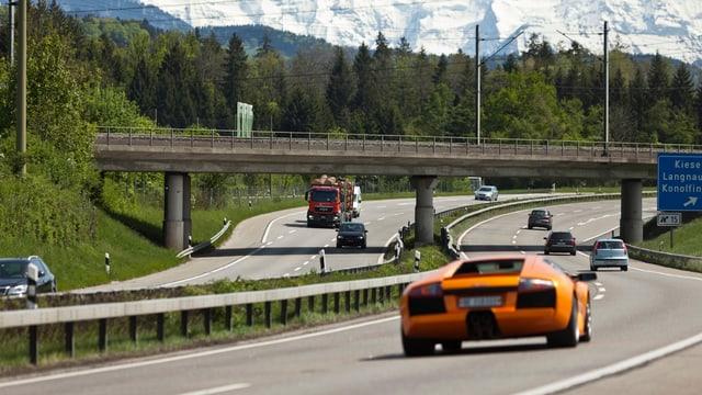 Autobahn mit einigen Autos, im Vordergrund ein orangefarbener Porsche.