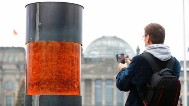 Ein Mann macht ein Handyfoto des temporären Mahnmals vor dem Reichstagsgebäude.