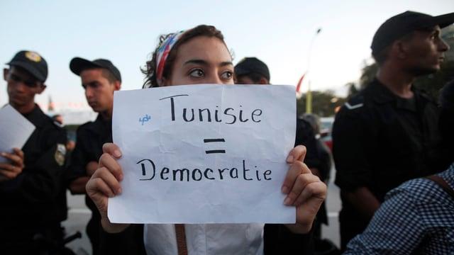 Eine Frau mit einem Schild, darauf steht: «Tunesien = Demokratie»