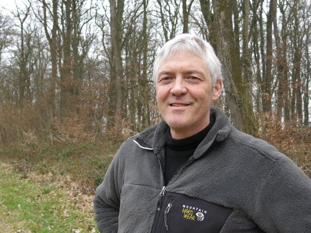 Markus Lack steht im Wald und schaut freundlich in die Kamera.