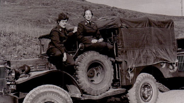 schwarzweiss Foto mit Gret Studach auf einem Dodge mit einer anderen Frau