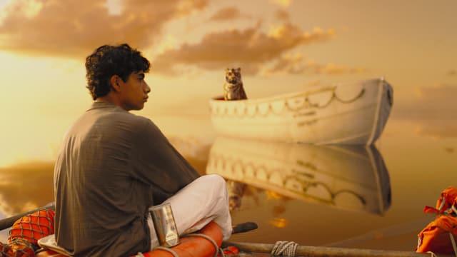 Ein Junge sitzt mit einem Tiger in einem Rettungsboot inmitten des Ozeans.