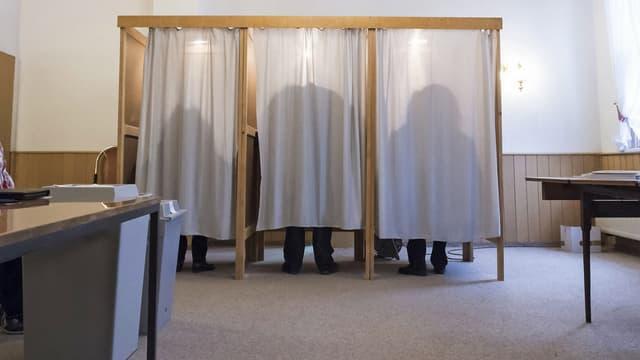 Sihouetten von drei Menschen in drei Wahlkabinen