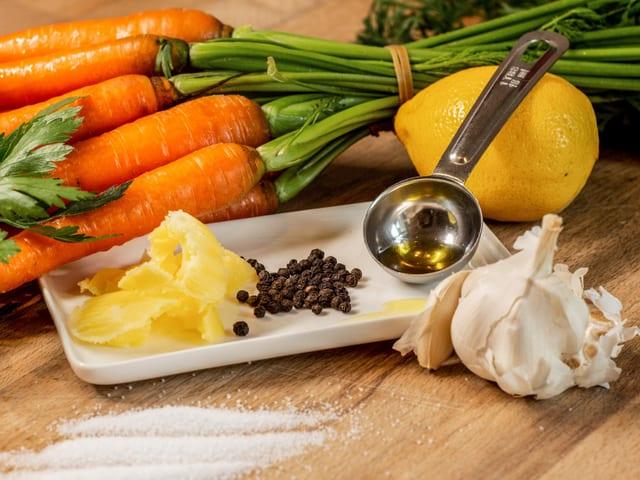 Auf einem Tisch liegen ein Bund Rüebli, eine Zitrone, Pfeffer, Salz, Knoblauch, Olivenöl