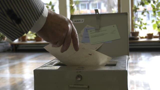 Hand, die einen Wahlzettel in Wahlurne wirft