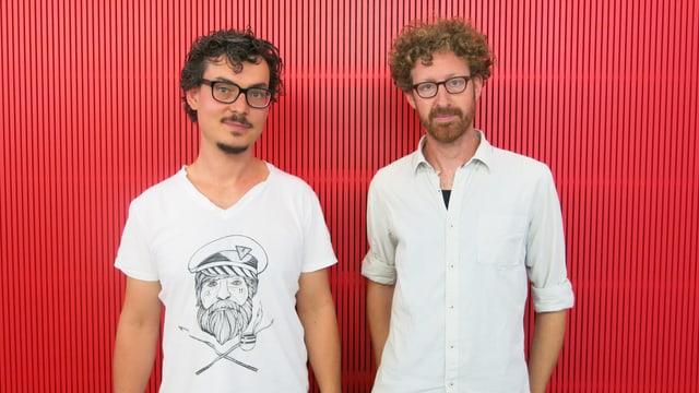 Matthias Baechthold und Roland Fischer stehen vor einer roten Wand.