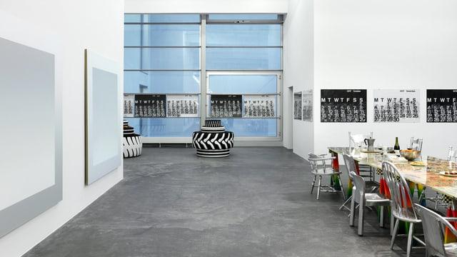 Ein grosser Raum: Darin eine Tafel und schwarz-weisse Bilder an der Wand.