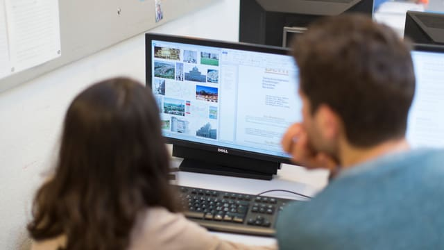 Ein Lehrer und eine Schülerin vor einem Computerbildschirm