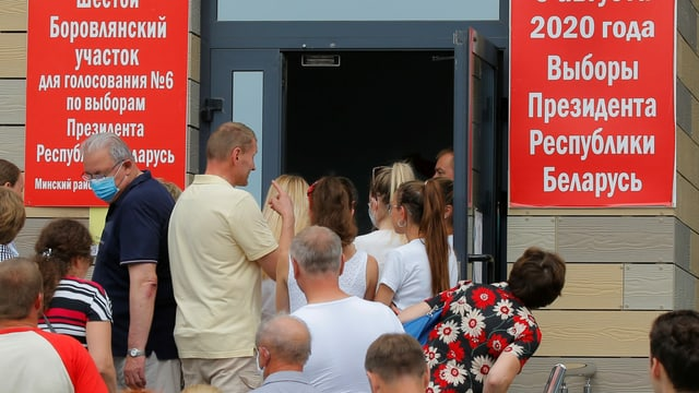 Leute vor Wahllokal.