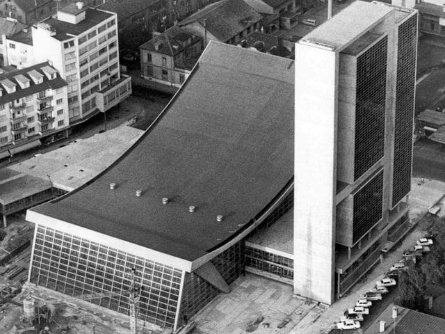 Das Kongresshaus Biel: Es besteht aus zwei Gebäudeteilen. Der erste ist ein Hochhaus mit einer Glasfront und das andere ist ein flacheres Gebäude mit nach innen geschwungener Decke. Die Fassade zur Strasse hin ist ebenfalls aus Glas.