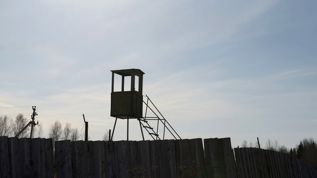 Gegenlichtaufnahme: Ein Wachtturm über einem Bretterzaun ragt in einen leicht bewölkten Himmel.