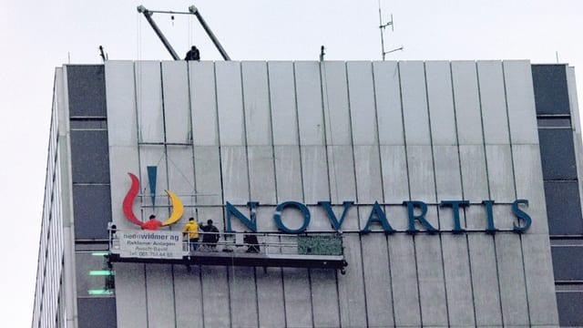 Il logo da Novartis vid il bajetg da la sedia principala a Basilea.