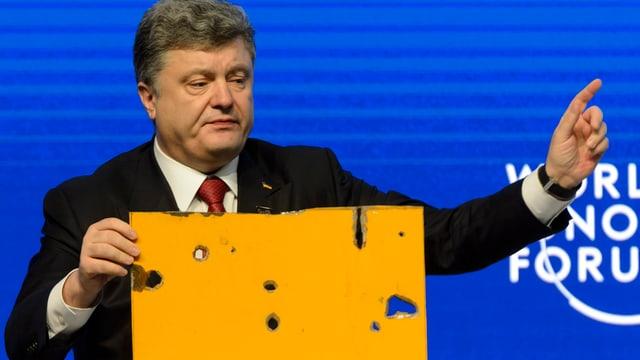 Petro Poroschenko hält am Rednerpult am WEF ein Teil eines beschossenen Busses in der Hand.