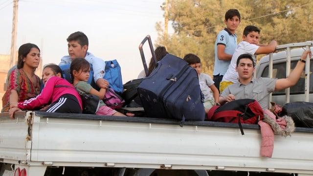 Flüchtlinge auf dem Dach eines Fahrzeugs