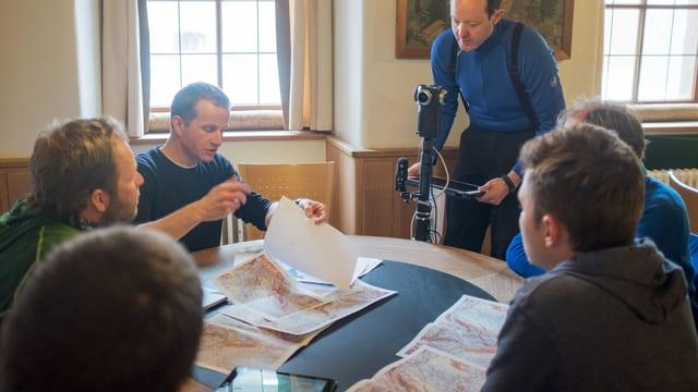 Eine Gruppe von Menschen sitzt mit Landeskarten und Wetterinformationen an einem Tisch. Hinter dem Tisch steht ein Mann mit einer Kamera.
