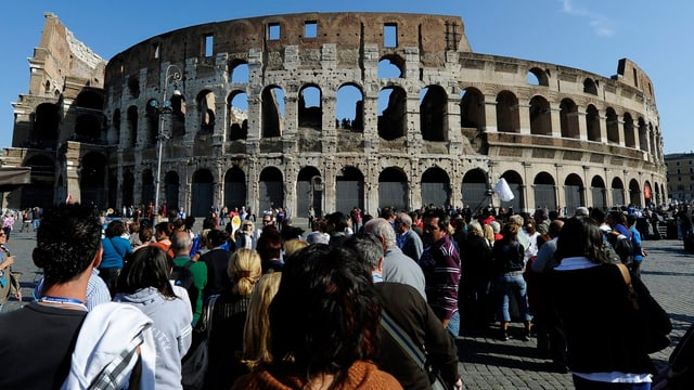Vor dem Kolosseum in Rom stehen Touristen an.