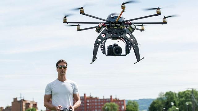 Mann mit Fernsteuerung und Drohne