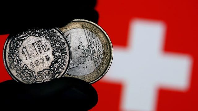 Ein Ein-Franken-Stück neben einem Ein-Euro-Stück vor einer Schweizerflagge