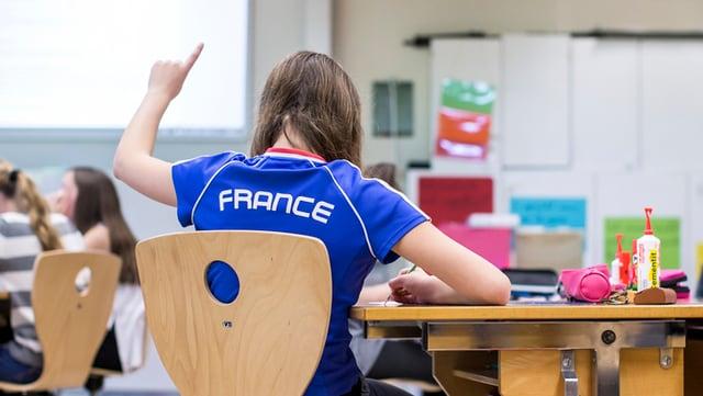 Ina scolara cun in T-Shirt blau e l'inscripziun France sesa en in baun da scola e tegn si il det.