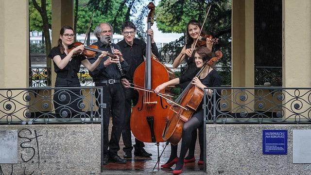 Drei Musikerinnen und zwei Musiker in einem Pavillon.