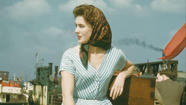 Nahaufnahme einer Frau, die am Hafen sitzt und aus dem Bild schaut.