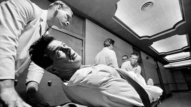 Ein Mann wird gefesselt auf einer Spitalliege weggeschoben und blickt panisch nach hinten.