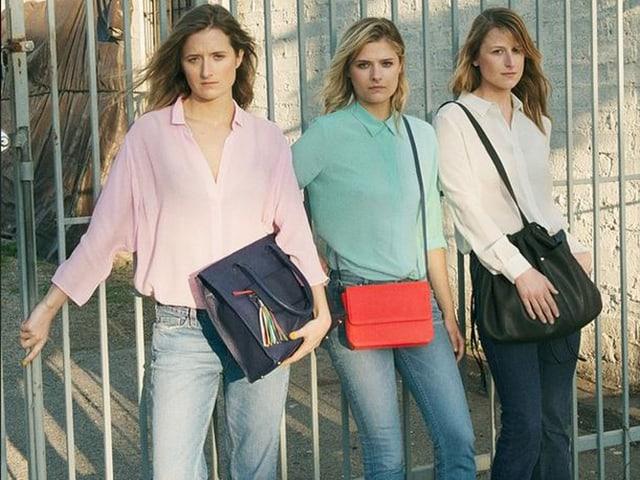 Drei junge Freuen mit Handtaschen nebeneinander stehend.