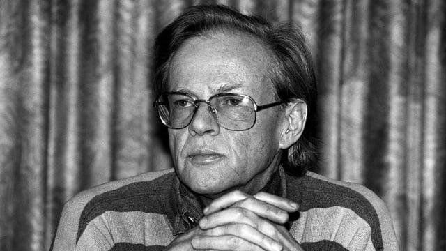 Ein Schwarzweissbild eines Mannes mit Brille, die Hände verschränkt.