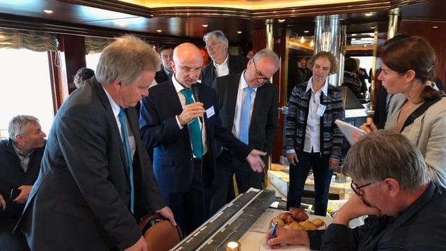 Harald Hetzenauer vom Institut für Seenforschung (Mitte mit Mikrofon) erklärt an Bord der MY Emily anhand einer Sedimentschicht, wie es dem Bodensee geht. Rechts neben ihm steht der Umweltminister von Baden-Württemberg, Franz Untersteller.