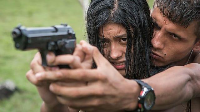 Ein Mann zeigt einer Frau, wie sie schiessen soll.
