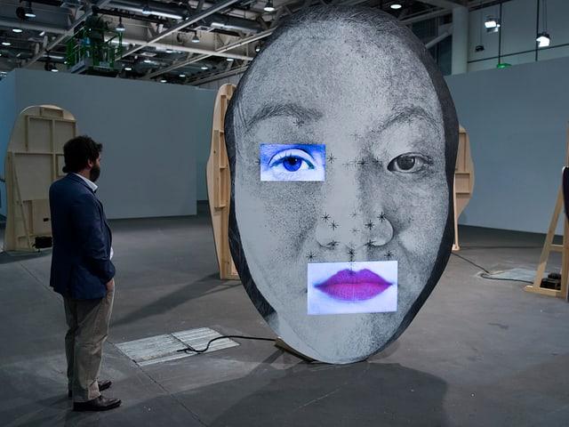 Ein Besucher blickt auf ein überdimensionales Gesicht.