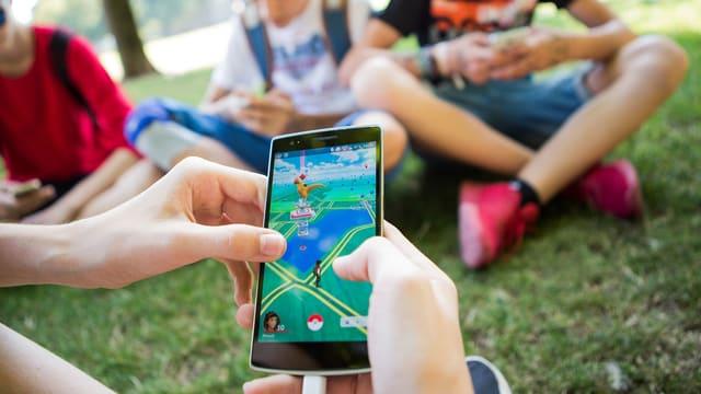 Jugendliche spielen in einem Park auf ihrem Handy.
