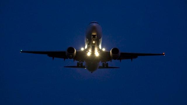 Flugzeug im Landeanflug in der Nacht.