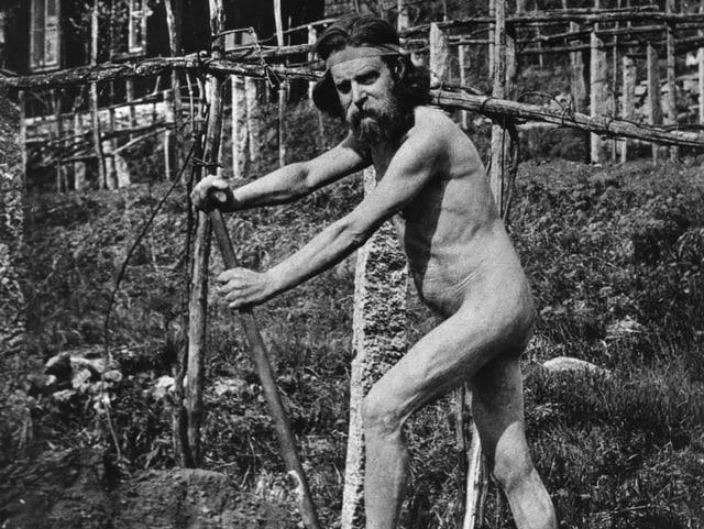 Nackter Mann mit Spaten bei der Gartenarbeit