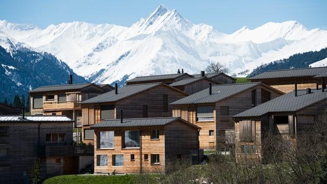 Einige Ferienwohnung und eine scheebedeckte Berglandschaft im Hintergrund