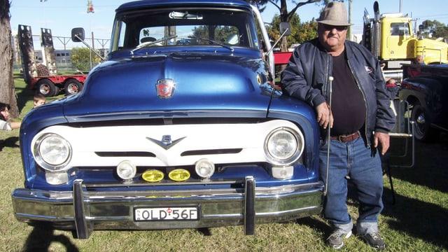 Besitzerstolz in Australien: Ein älterer Mann posiert neben seinem blauen Oldtimer-Truck.