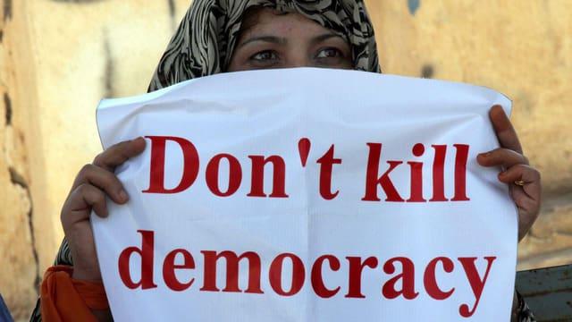 """Eine Studentin der Bewegung gegen Wahlbetrug hält ein Plakat: """"Don't kill democracy""""."""
