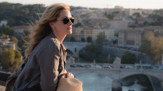 Eine Frau blickt nachdenklich in eine weite Landschaft.