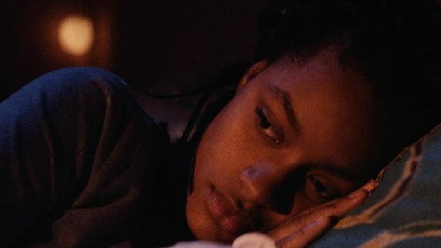 Eine junge schwarze Frau liegt im Bett.