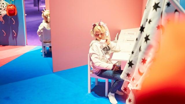 Mädchen sitzt am Telefon in einem rosa zimmer