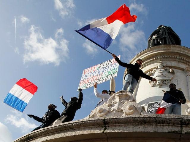 Jugendliche haben eine Statue auf dem Place de la Republique erklommen.